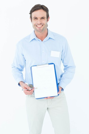 Portrait of happy businessman showing blank clipboard over white background photo
