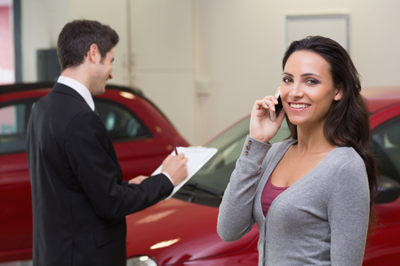 automobile dealership: Smiling woman calling someone with her mobile phone at new car showroom