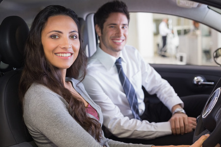 salesperson: Female driver at the wheel sitting in her car with salesperson at new car showroom