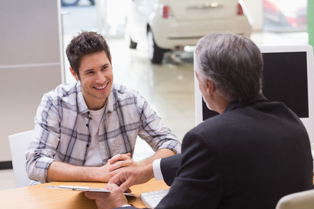 salesman: Salesman showing client where to sign the deal at new car showroom Stock Photo