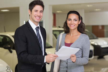 Salesperson showing clipboard to sign to customer at new car showroom
