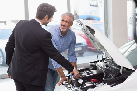 engine bonnet: Two men looking at a car engine at new car showroom Stock Photo