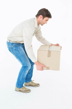 Full length of delivery man picking cardboard box against white background