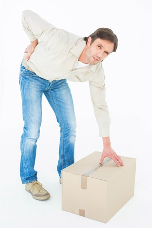 wincing: Full length portrait of delivery man with cardboard box suffering from back ache on white background Stock Photo