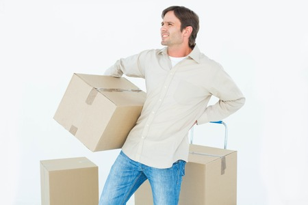 back ache: Upset delivery man with cardboard box suffering from back ache on white background Stock Photo
