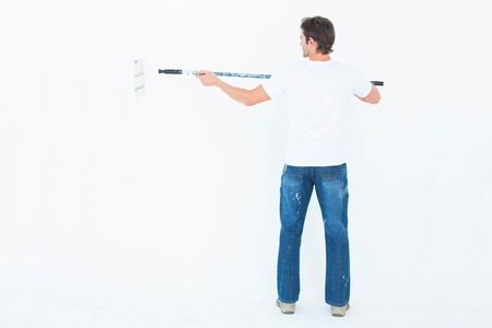 redecorating: Full length rear view of man using paint roller on white background Stock Photo