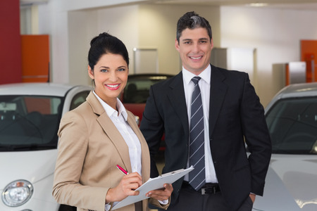suit man: Business team smiling at camera at new car showroom