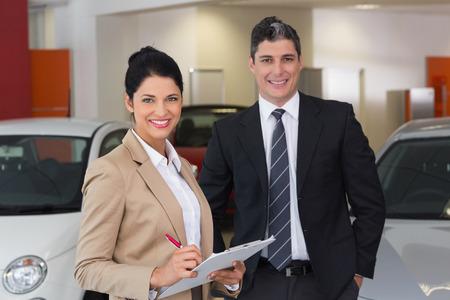 traje: Equipo de negocios sonriendo a la c�mara en la nueva exposici�n de coches