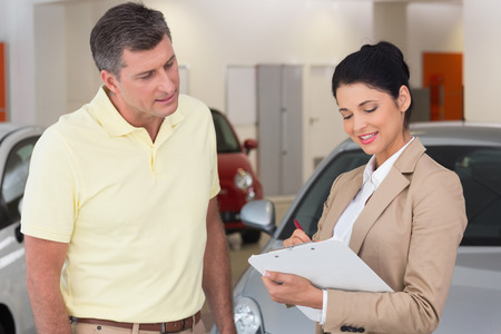 undersign: Smiling businessman undersign a car contract at new car showroom Stock Photo