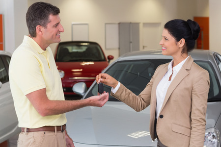 ?  ?       ?  ?      ?  ?     ?  ?    ?  ? �female: Empresaria dando la llave del coche de feliz al cliente al nuevo concesionario de coches Sonriente Foto de archivo