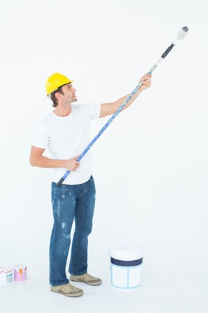 redecorating: Full length side view of man painting on white background Stock Photo