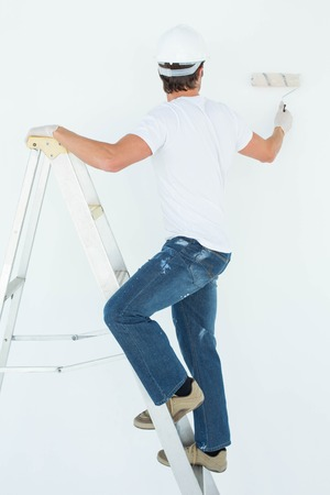 redecorating: Full length of man on ladder painting with roller over white background