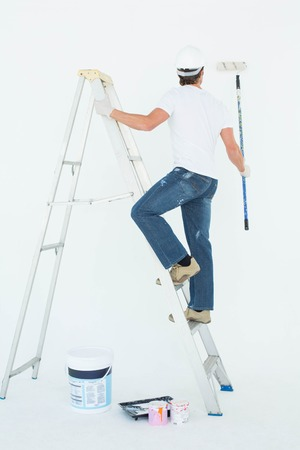 ladder safety: Full length rear view of man on ladder painting with roller over white background