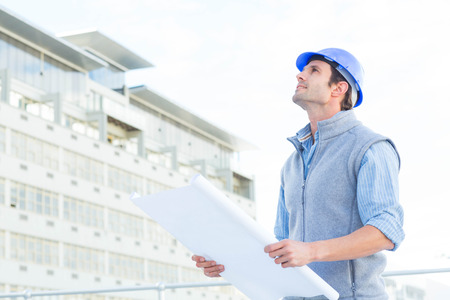 think safety: Male architect looking up while holding blueprint outside building