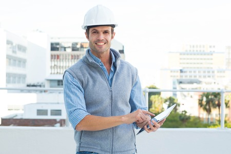 Portrait of happy male architect using digital tablet outdoors photo