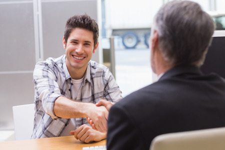 reaching hands: Smiling customer shaking a salesman hand at new car showroom Stock Photo