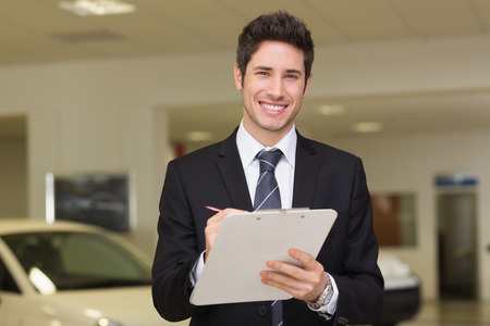 noting: Smiling businessman writing on clipboard at new car showroom