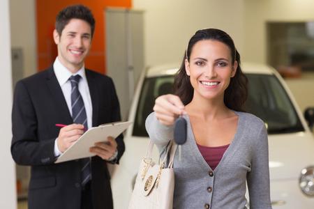 car showroom: Happy customer holding a car key at new car showroom
