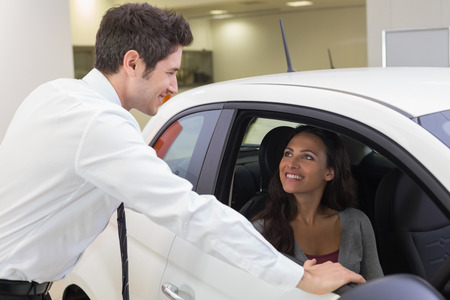 happy client: Salesperson speaking with happy client at new car showroom