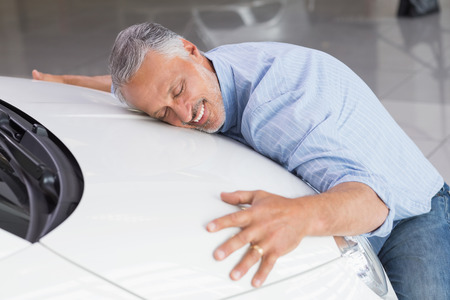 Smiling man hugging a white car at new car showroom