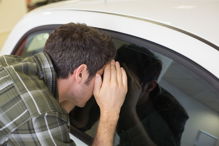looking inside: Man looking inside a car at new car showroom Stock Photo