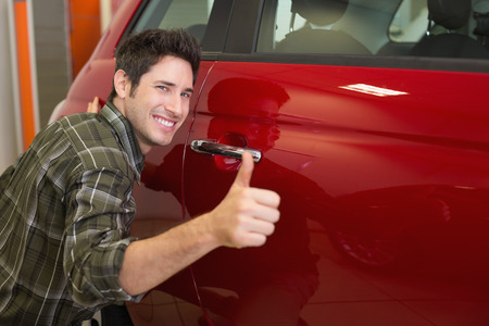 hand  up: Smiling man hugging a red car while giving thumbs up at new car showroom Stock Photo