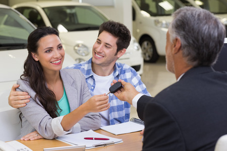Salesman giving car keys to a couple at new car showroom Stock Photo