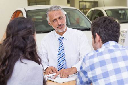 salesperson: Salesperson pointing something on booklet at new car showroom