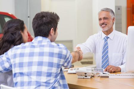 car showroom: Smiling salesman shaking a customer hand at new car showroom