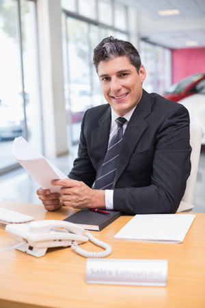 salesperson: Smiling salesperson holding a document at new car showroom