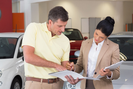 salesperson: Salesperson talking with her customer while holding a booket at new car showroom