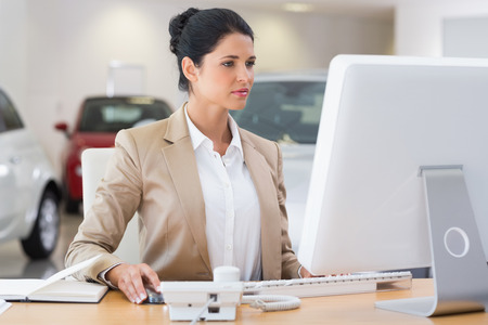Focused businesswoman working on computer at new car showroom