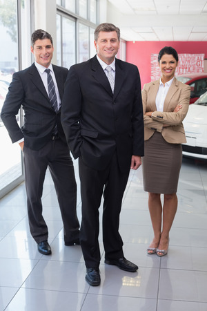 automobile dealership: Smiling business team standing together at new car showroom