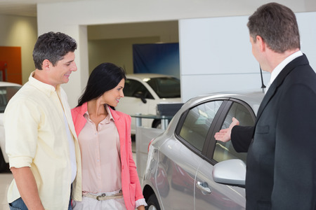 car salesperson: Businessman showing a car to a couple at new car showroom Stock Photo