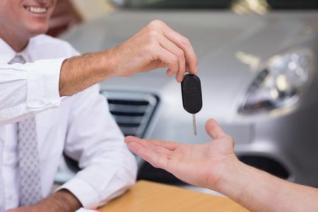 car showroom: Salesman giving a customer car keys at new car showroom