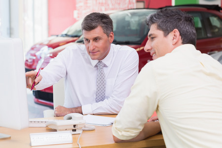 car showroom: Businessman pointing his finger at screen at new car showroom Stock Photo