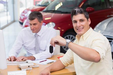 Smiling customer showing his new key at new car showroom photo