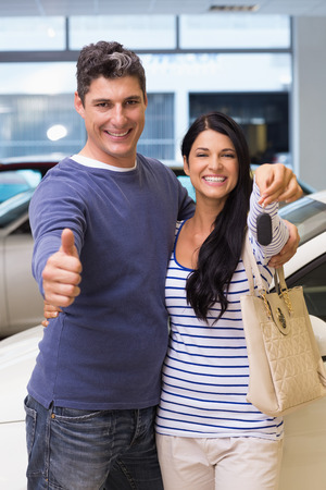 mid adult couple: Smiling couple holding their new car key at new car showroom