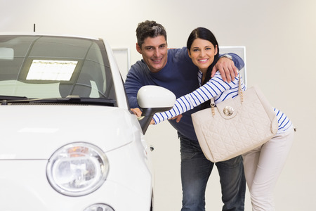 car showroom: Smiling couple looking inside a car at new car showroom Stock Photo