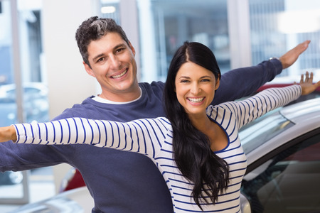 envisioning: Happy couple standing with arms outstretched at new car showroom