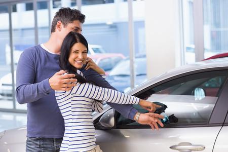 car showroom: Smiling woman presenting her new car at new car showroom