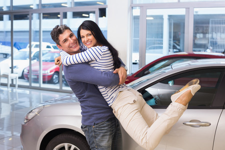 people buying: Smiling couple hugging and smiling at camera at new car showroom