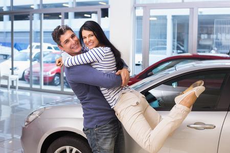 carro supermercado: Sonriente pareja abrazándose y sonriendo a la cámara en la nueva exposición de coches Foto de archivo