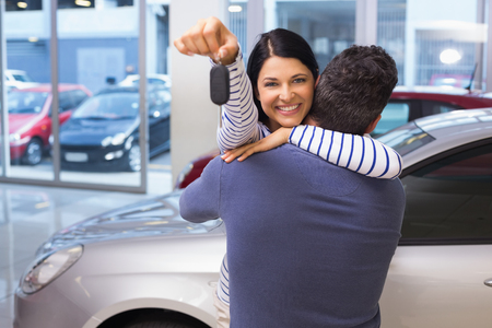 Portrait couple: Smiling couple hugging and holding their new key at new car showroom Stock Photo