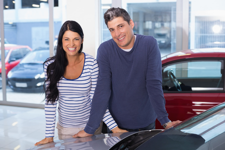 car showroom: Smiling couple leaning on car at new car showroom