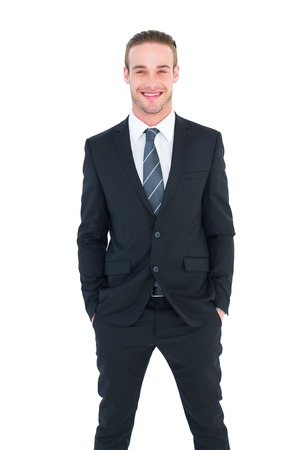 white suit: Smiling businessman in suit with hands in pocket posing on white background
