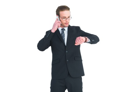 phoning: Serious businessman phoning while checking time on white background Stock Photo