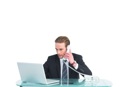 scowl: Serious businessman using laptop while phoning on white background