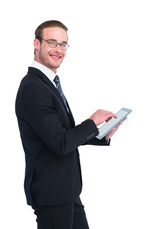 Happy businessman using his tablet pc on white background photo