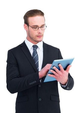 Unsmiling businessman using tablet pc on white background photo